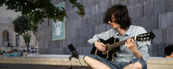 Guitar player recording his instrument and his voice on a DGT 650 in a park